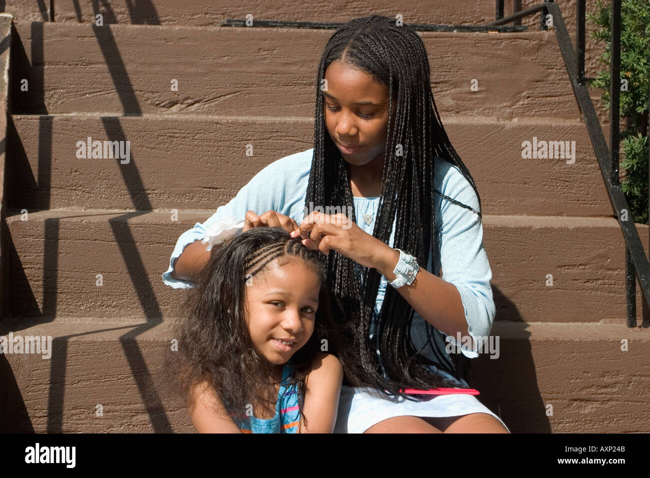 Teenage African American Girl Sitting On Steps And Braiding Hair Of