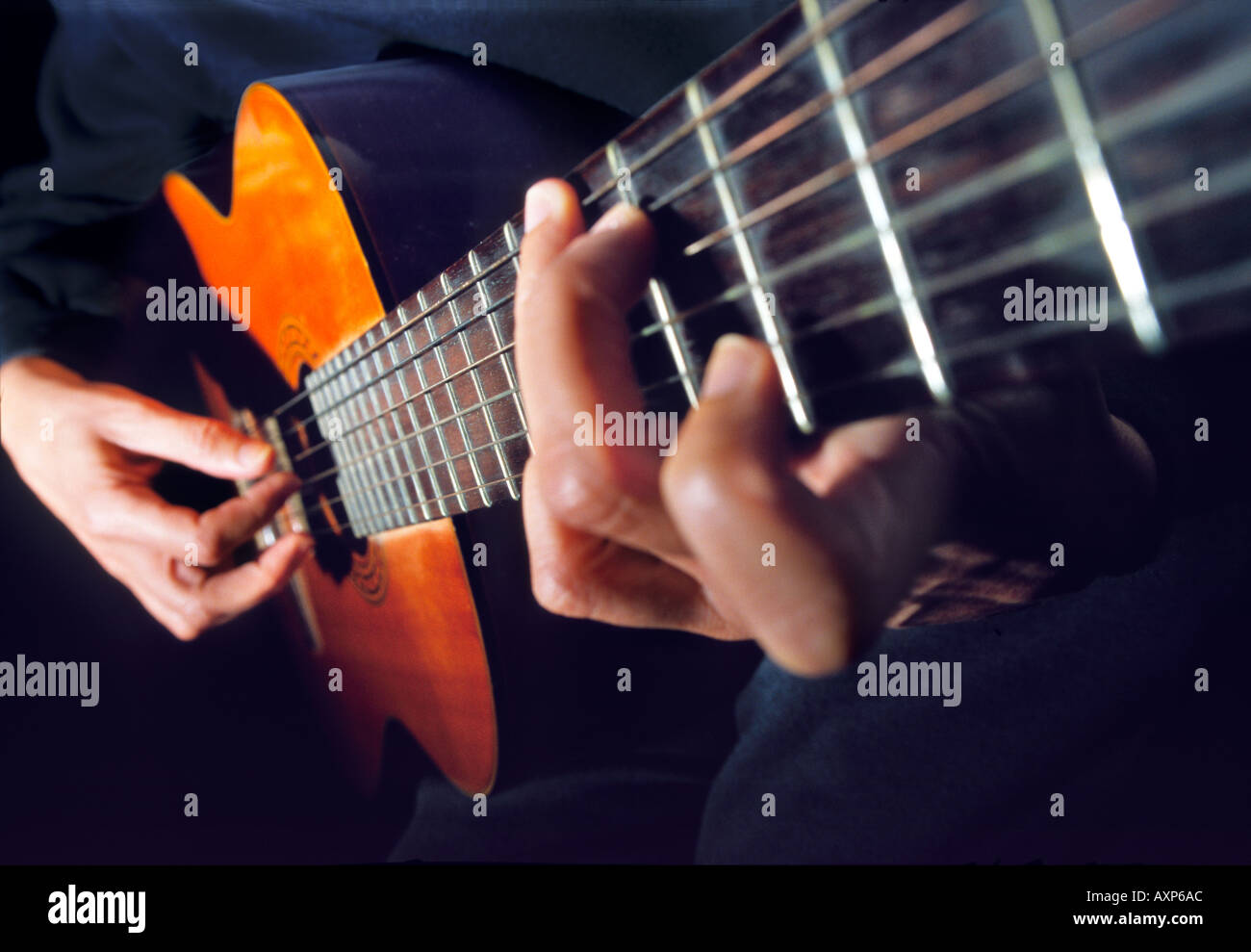 Hands on guitar strings - Stock Image