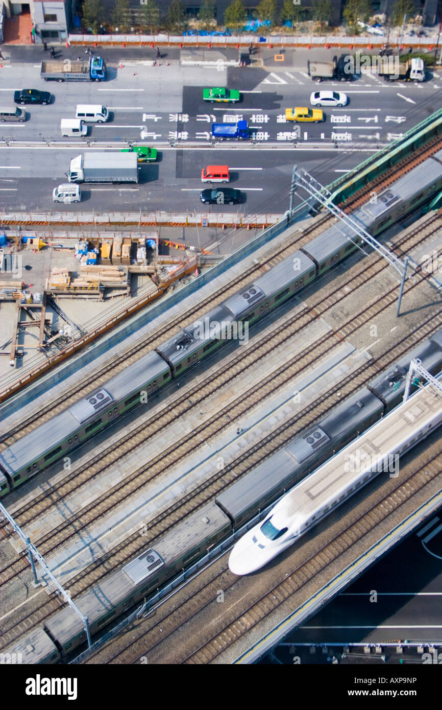 Aeiral view of trains passing on tracks and cars and trucks driving on street below in Shiodome section of Tokyo, - Stock Image