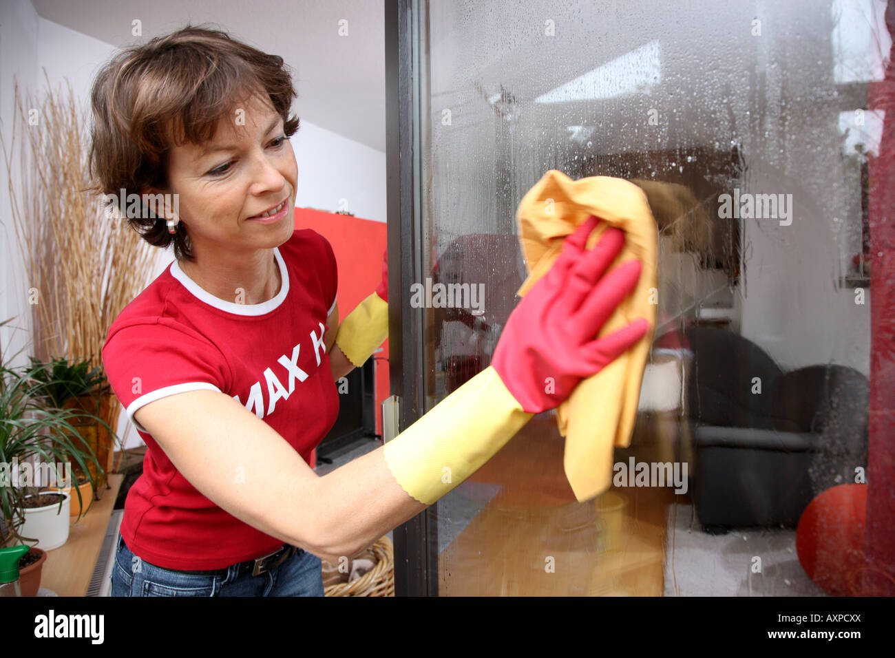 Household woman is wiping windows - Stock Image