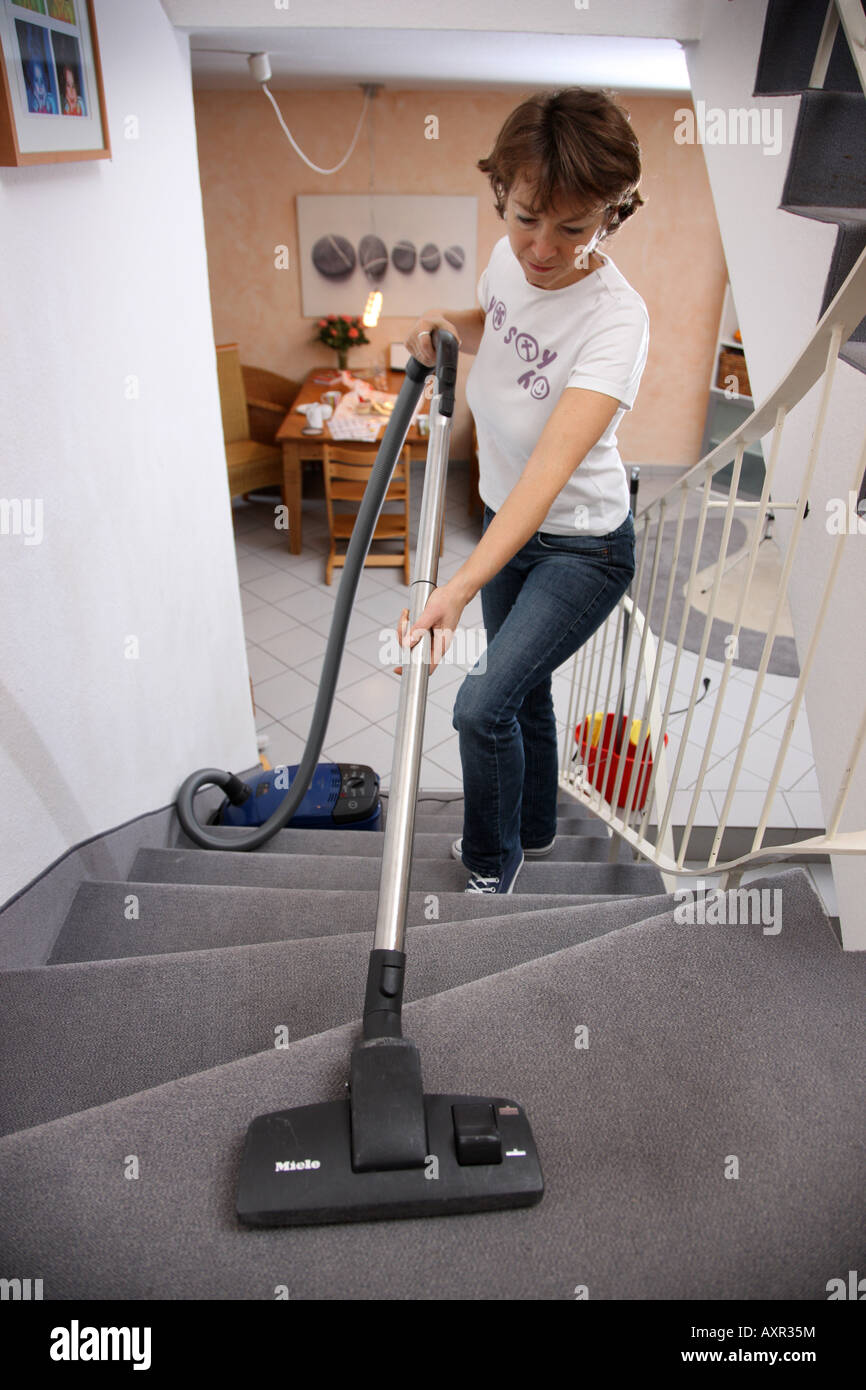 Household woman with a vaccum cleaner in a private house - Stock Image