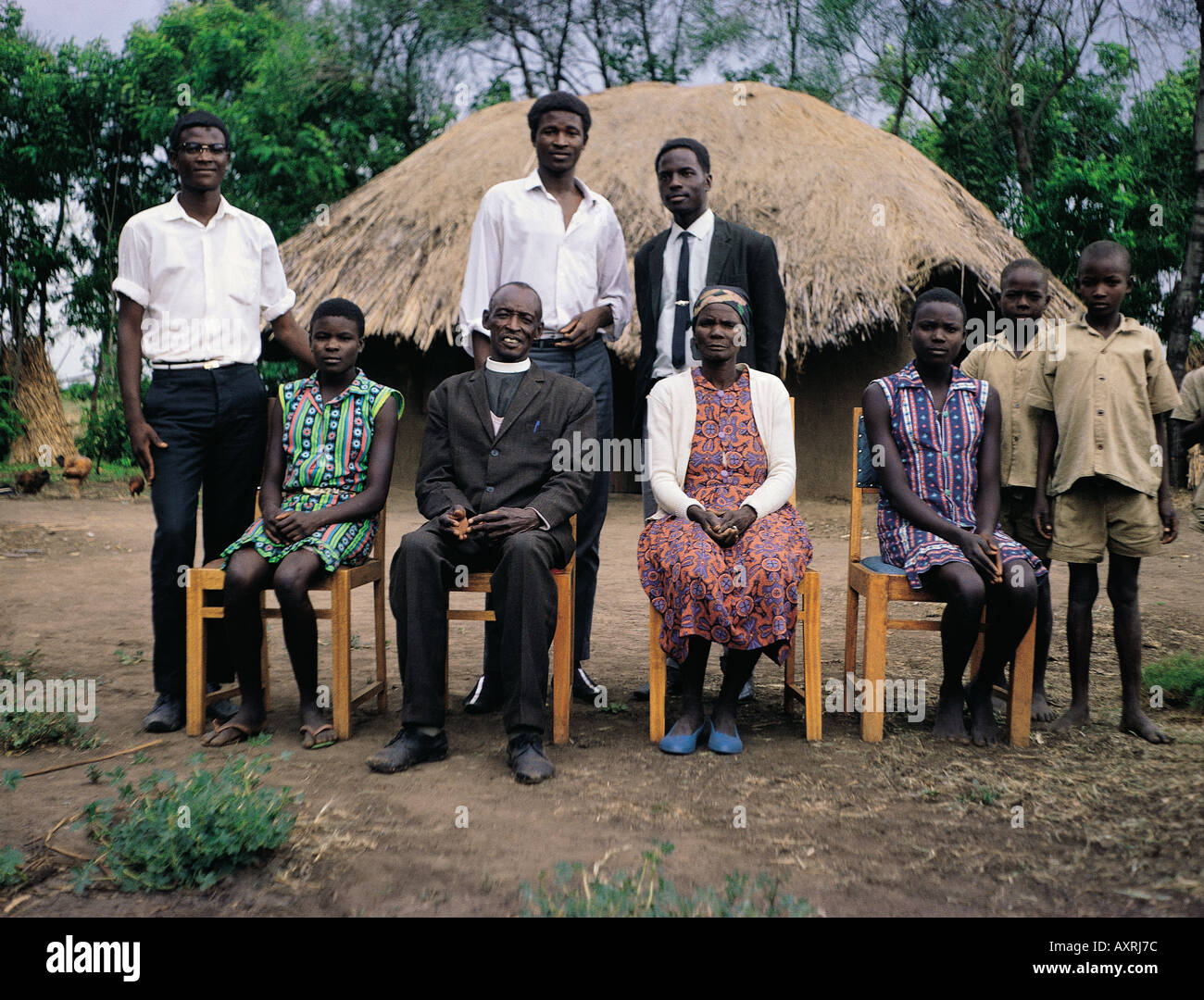 Luo Pastor with his wife and extended family outside their house in South Nyanza western Kenya East Africa - Stock Image