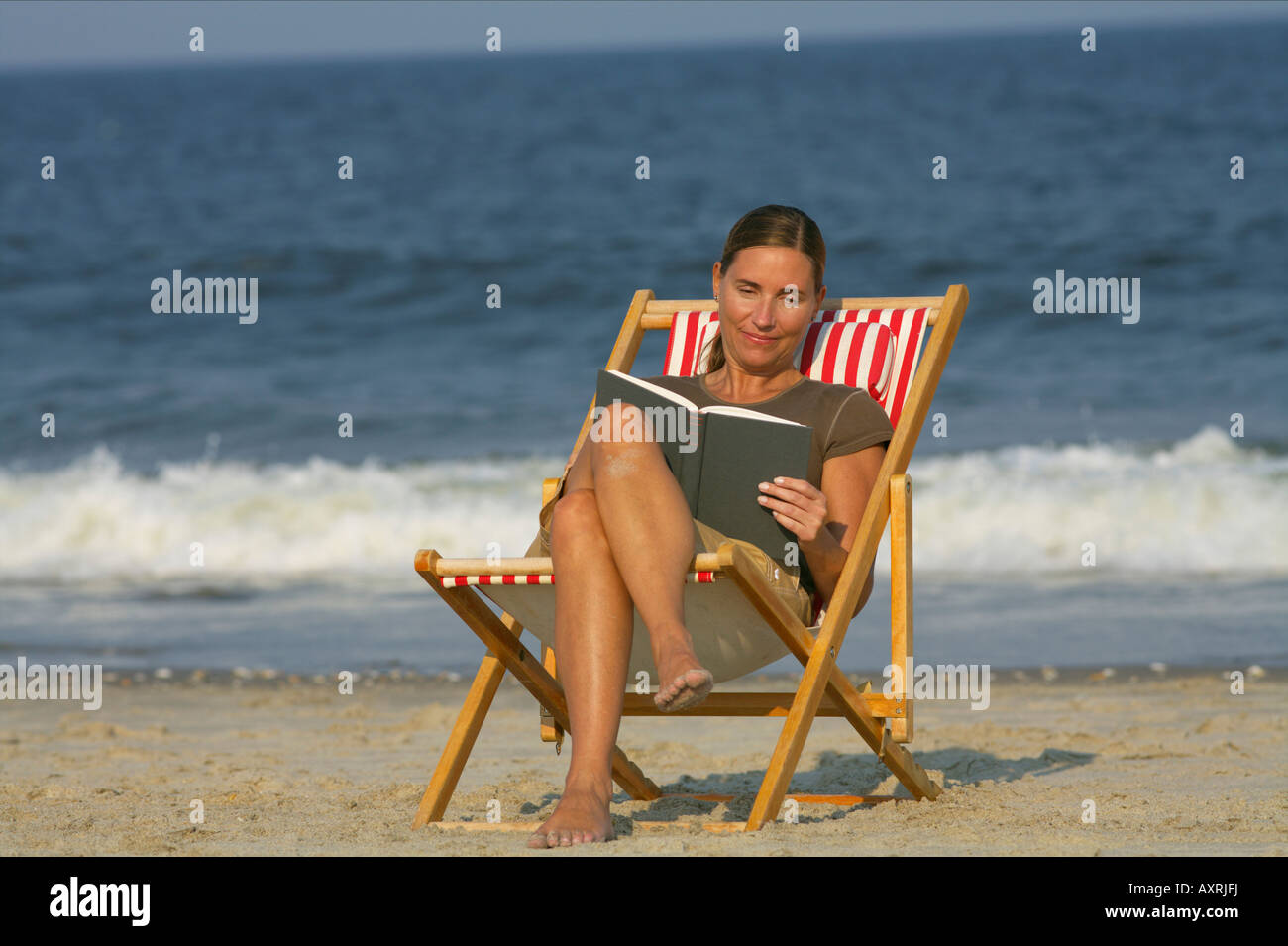 Woman Sitting On A Beach Chair While Reading Stock Photo Alamy