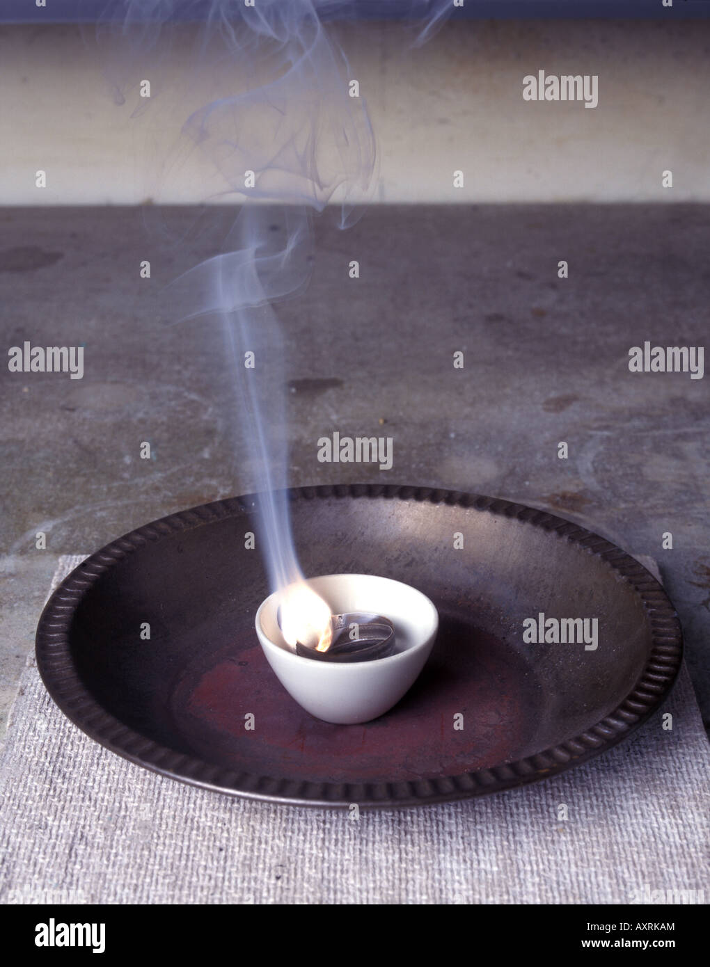 Magnesium ribbon burning in a crucible - Stock Image