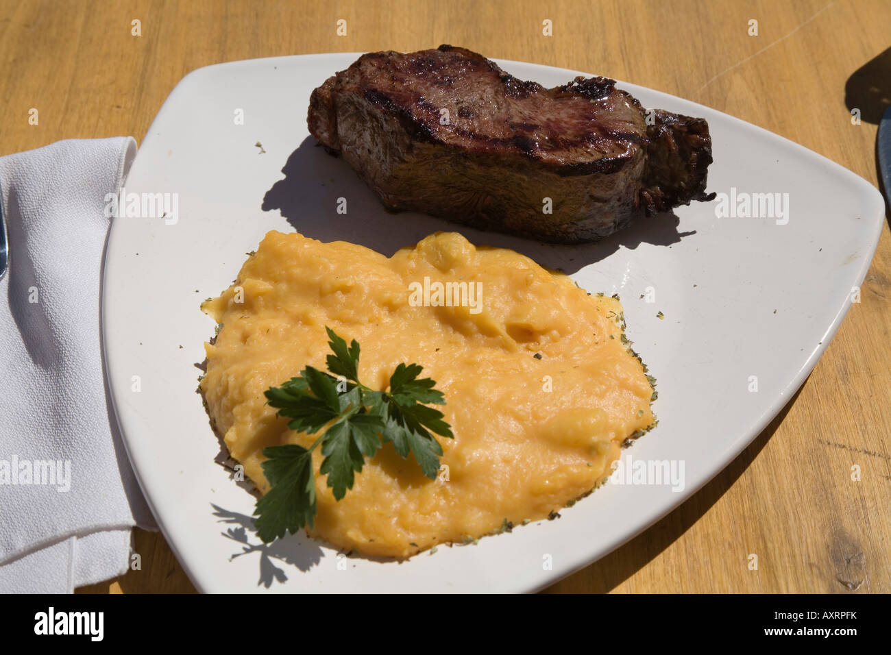 Steak on plate, half portion, ready to eat - Stock Image