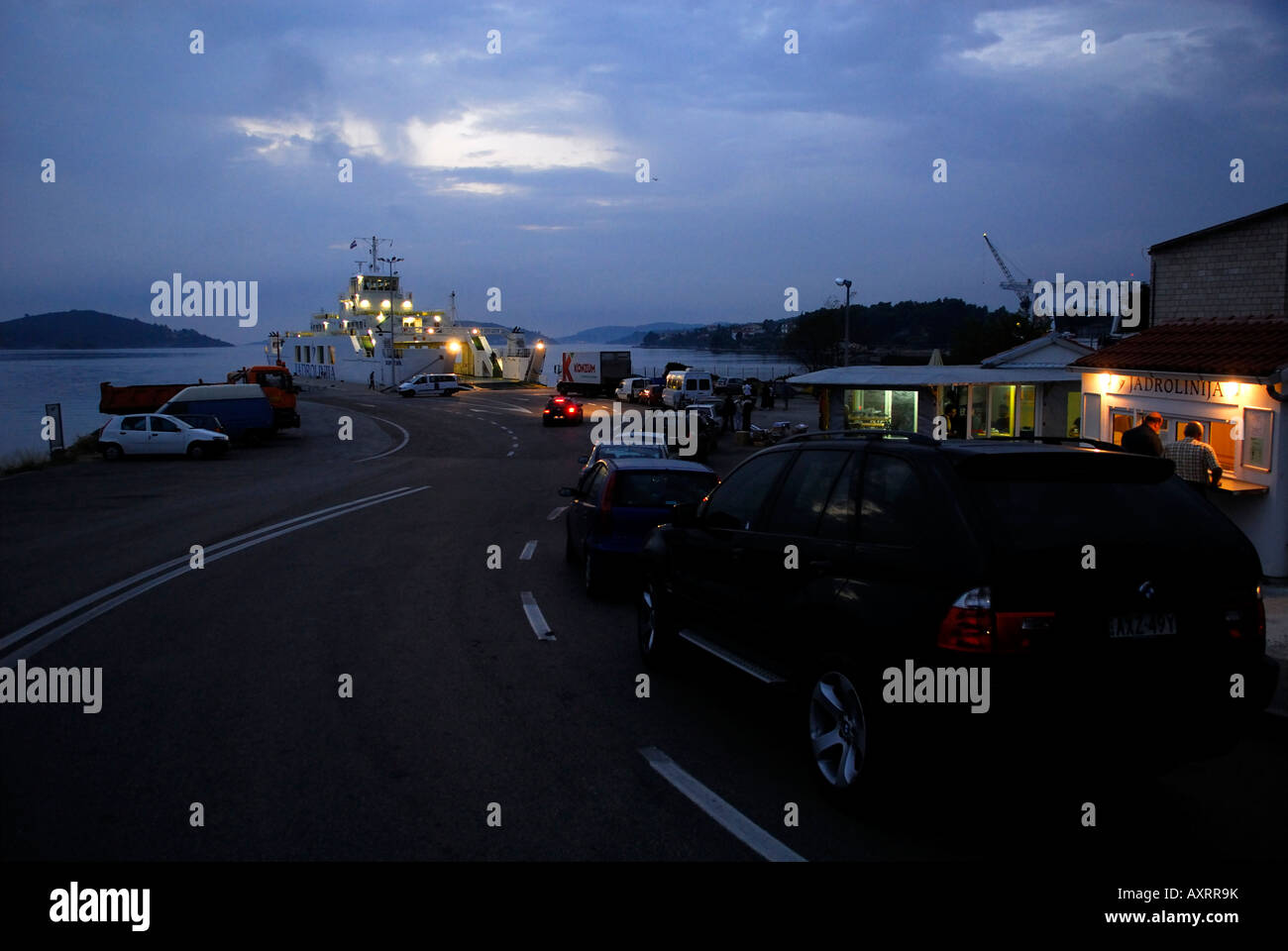 Cars and trucks lined up waiting to board car-ferry at pre-dawn. Dubrovnik, Croatia - Stock Image