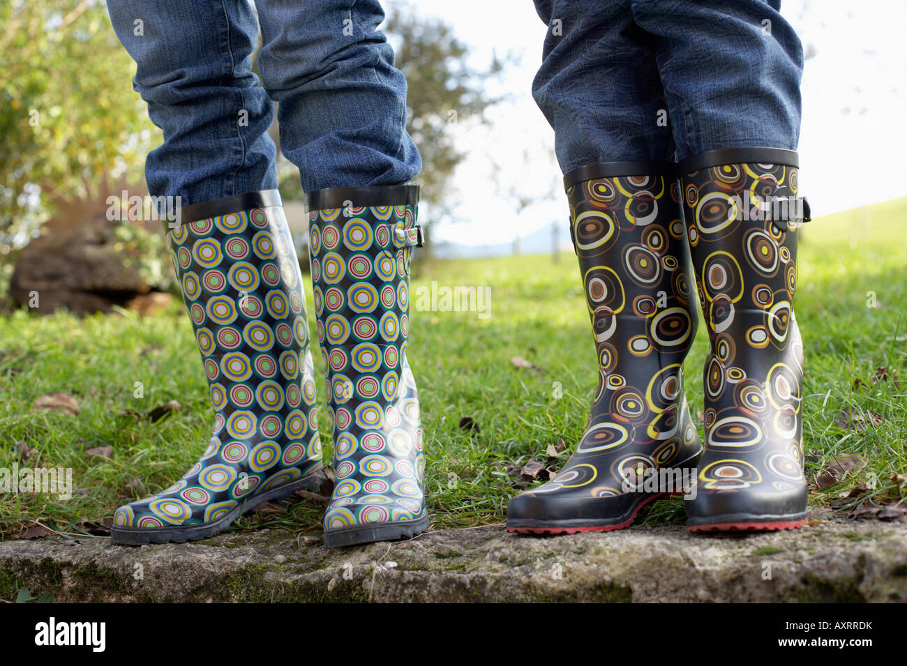Two people in rubber boots standing on a wall, selective focus - Stock Image