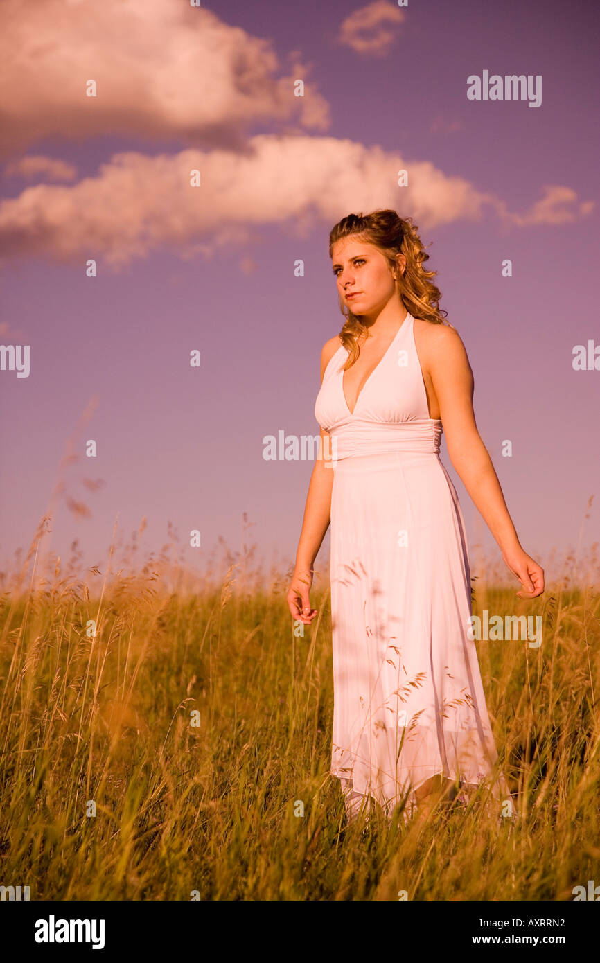 Woman standing in a field - Stock Image