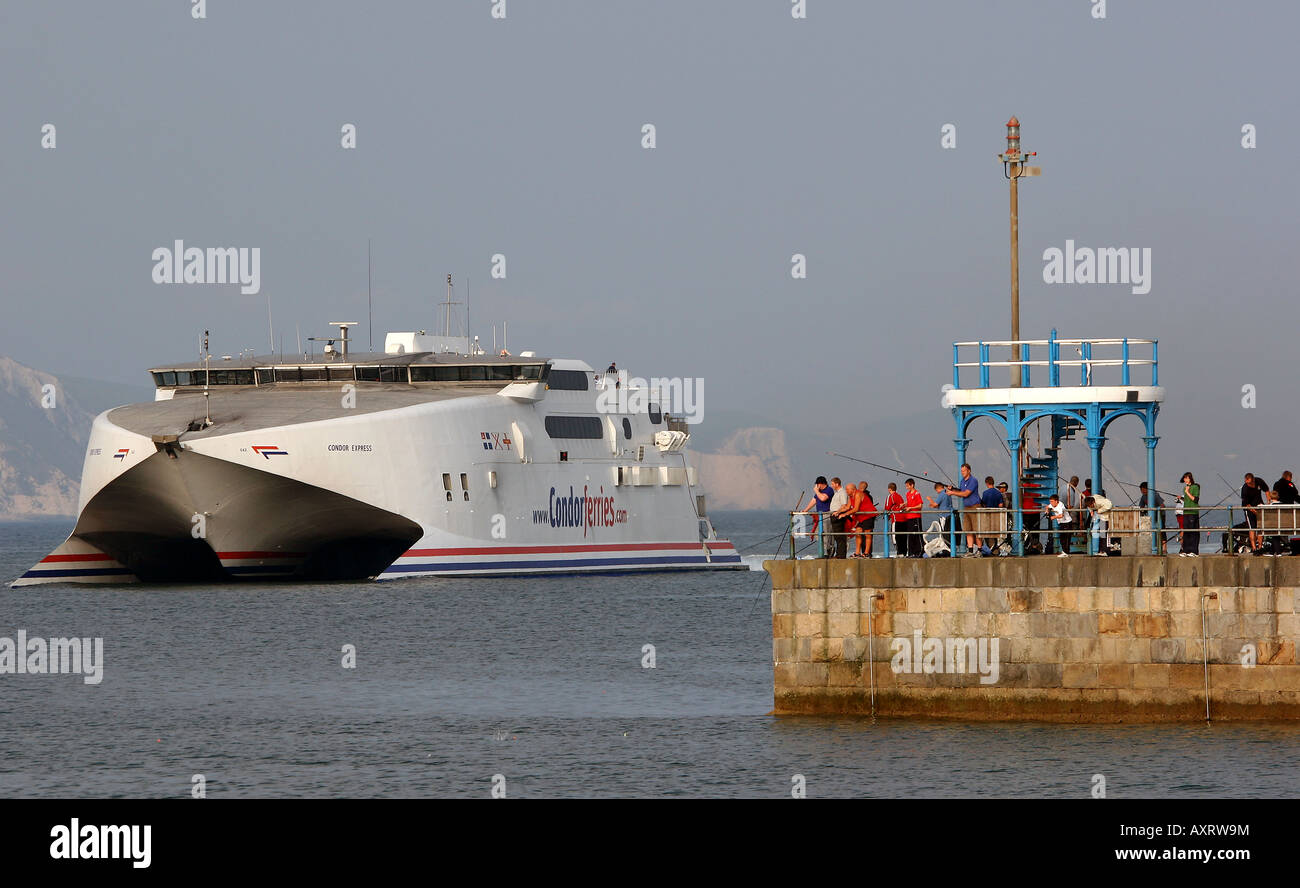 Condor Express ferry from the Channel Islands enters Weymouth Harbour watched by fishermen fishing from the Stone - Stock Image