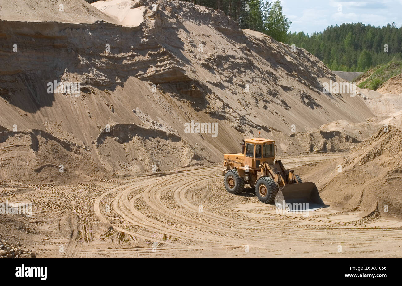Gravel pit and front loader . Digging sand and gravel from a glacial esker , Finland - Stock Image