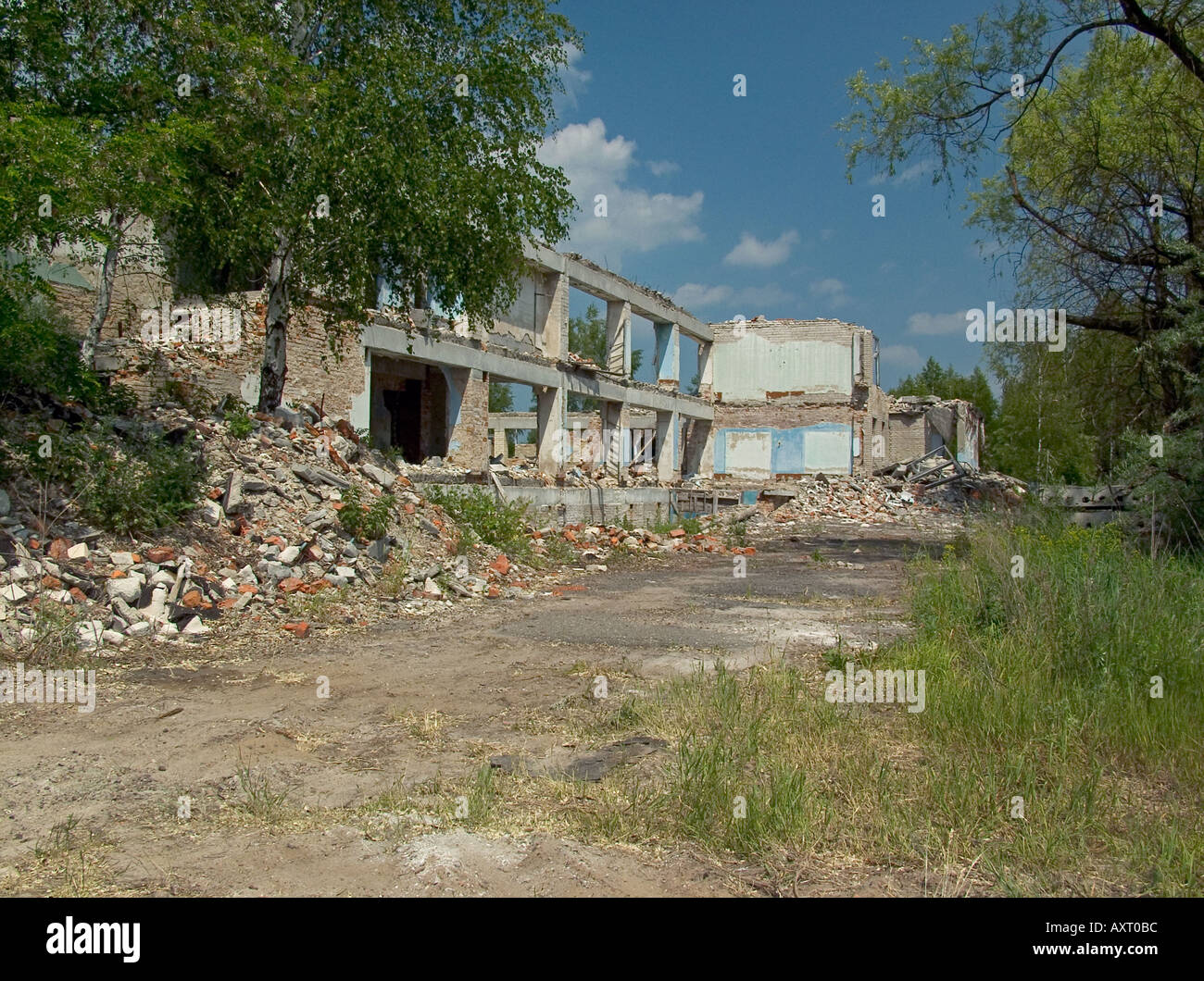 Street with abandoned derelict decaying buildings, collapsed window frame amidst rubble, trees, Chernobyl exclusion zone, Belarus Ukraine state border - Stock Image