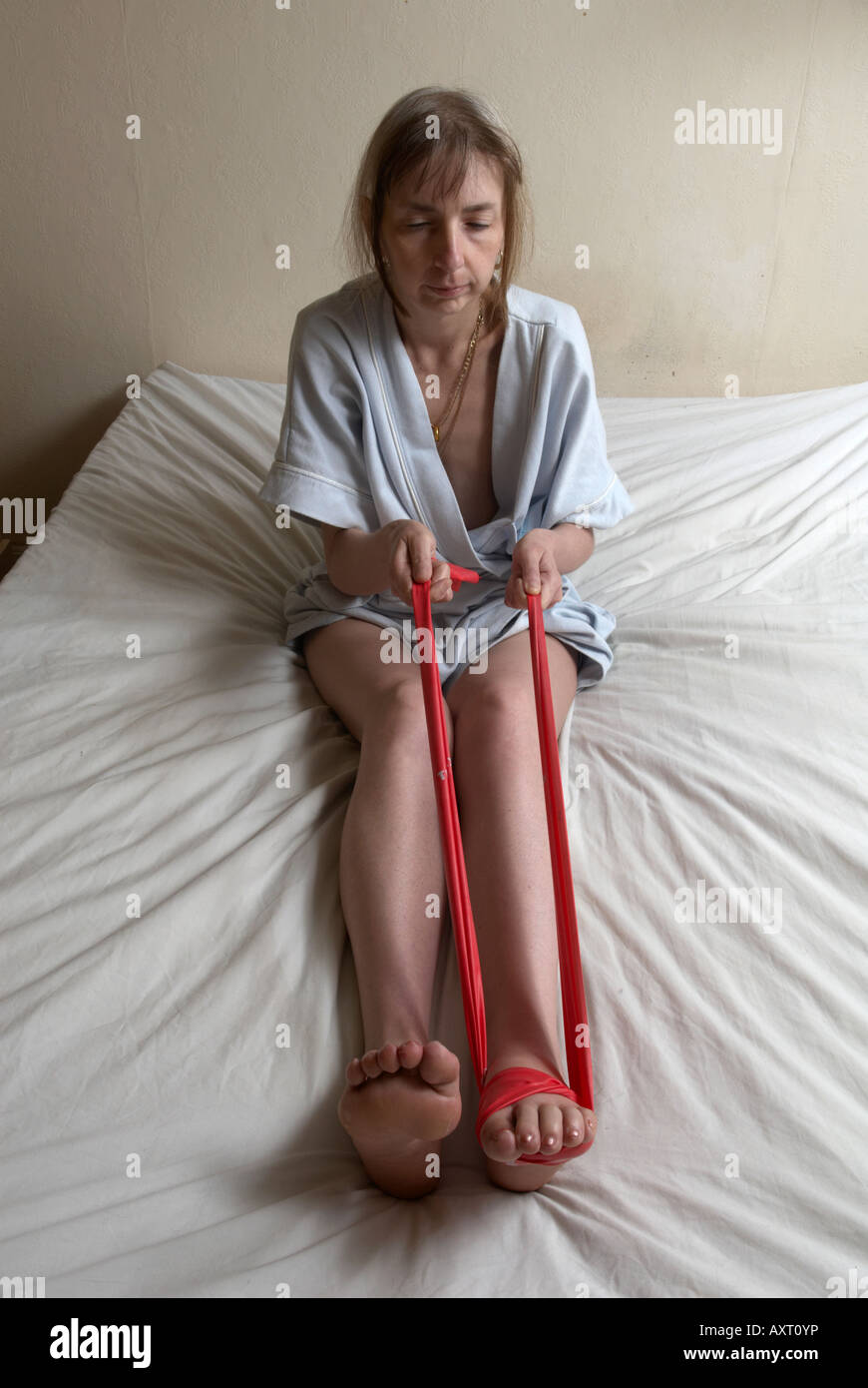 """Exercising feet when one has drop foot using bungee to pull up dropped foot, the toes of the left foot look """"dead"""" Stock Photo"""