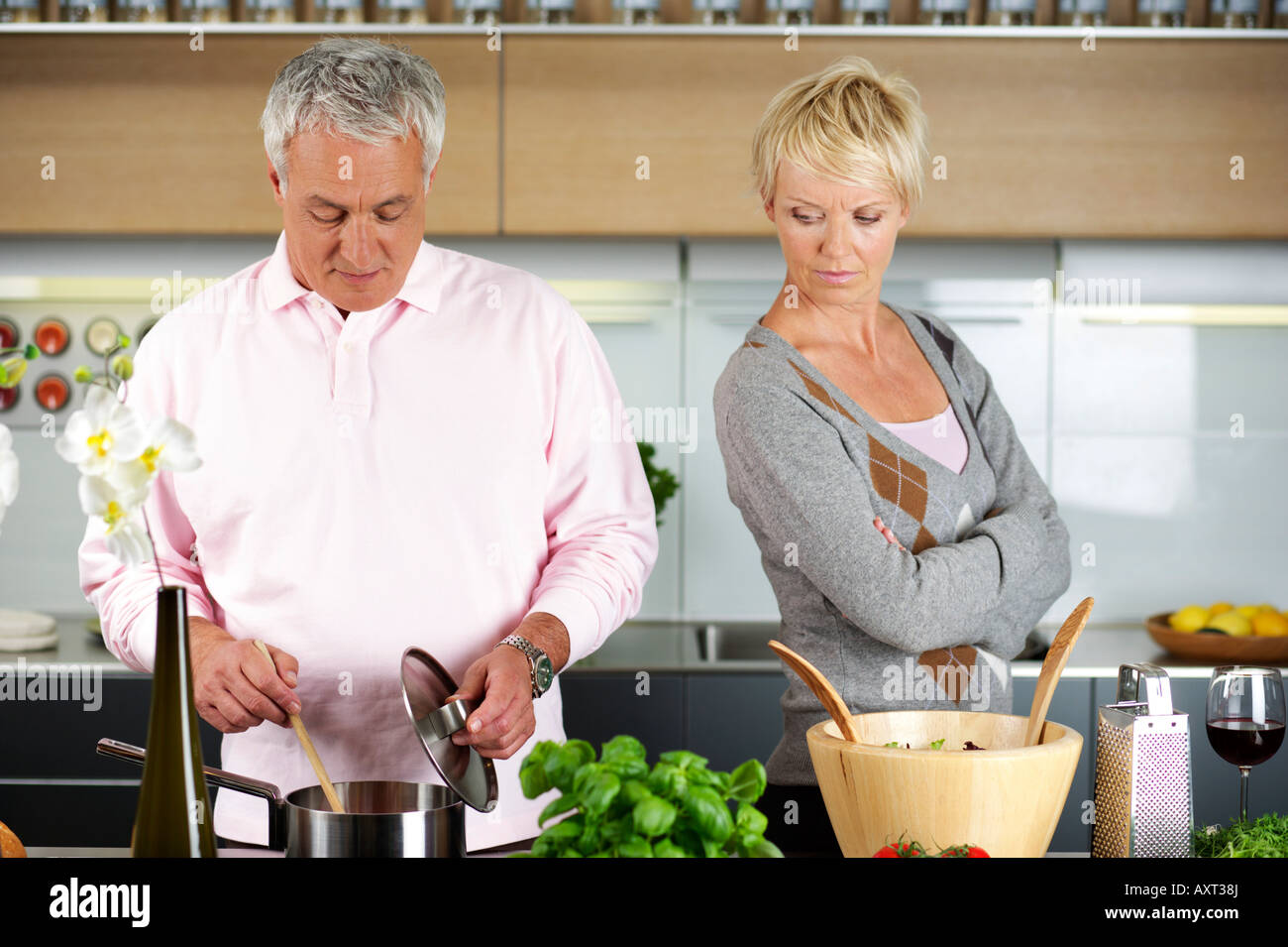 Blond woman turned away from a man who is cooking Stock Photo