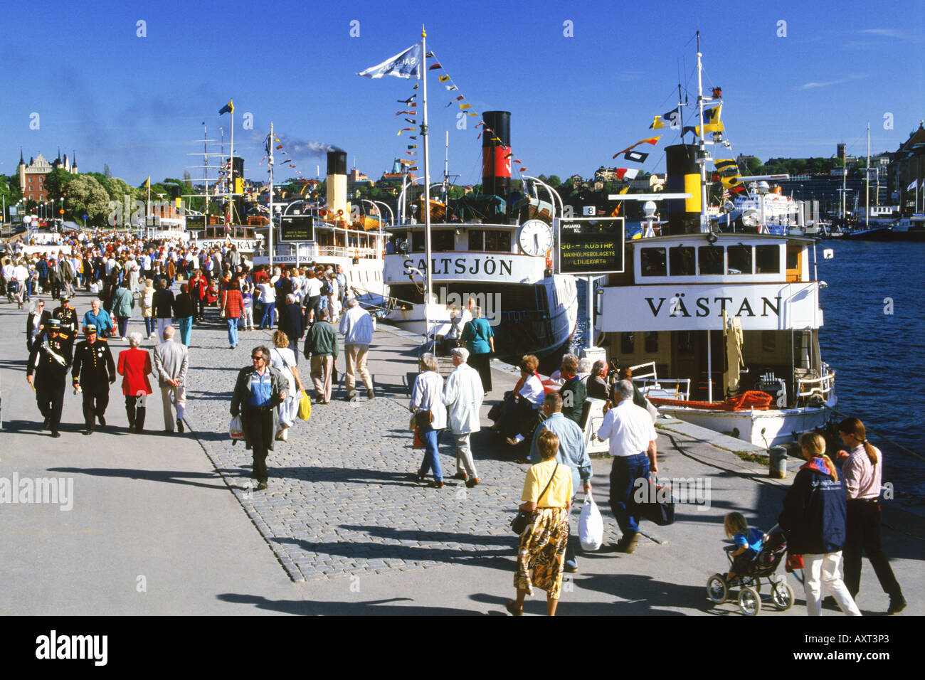 Passengers and steamships at Blasieholmen Island in front of Grand Hotel on Archipelago Boat Day in Stockholm - Stock Image