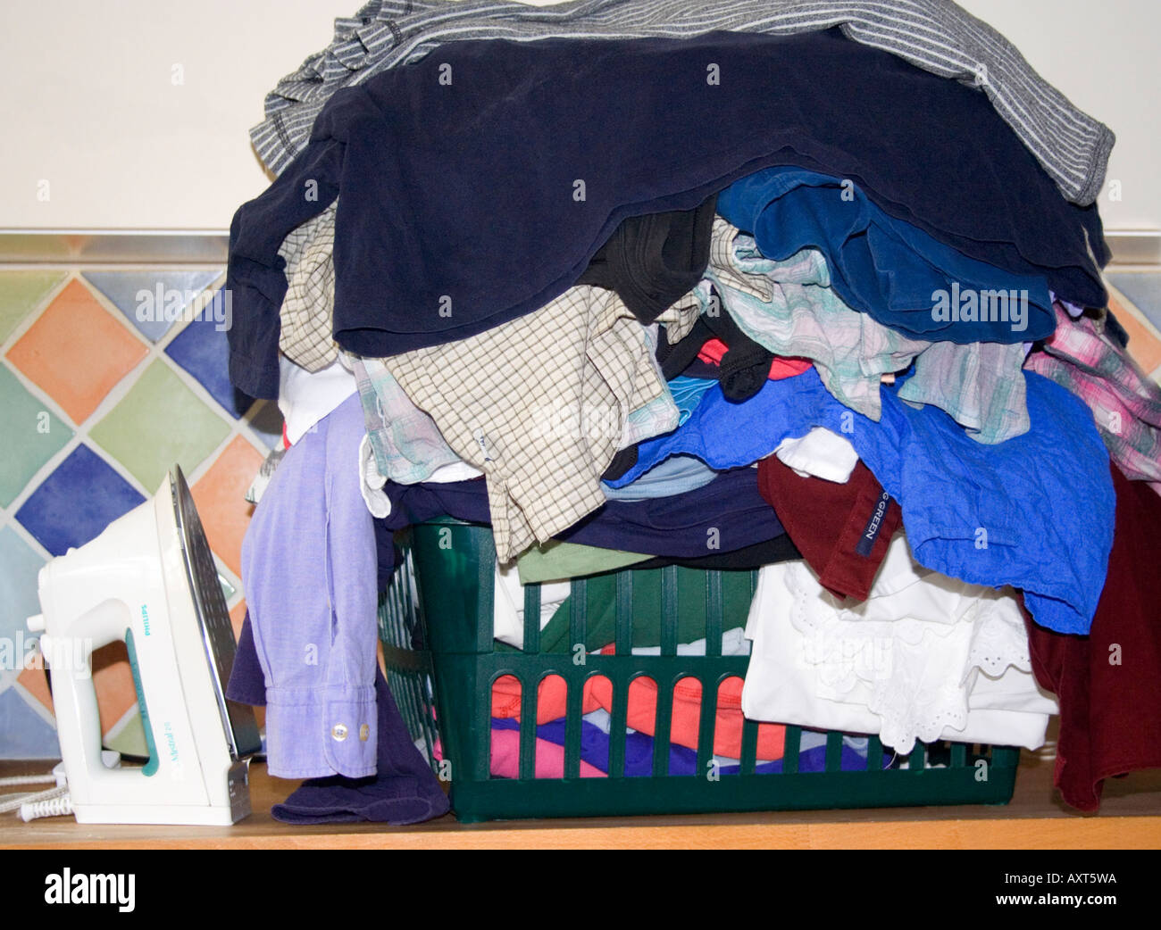 A pile of clothes. Ironing. Laundry basket. Steam iron. - Stock Image
