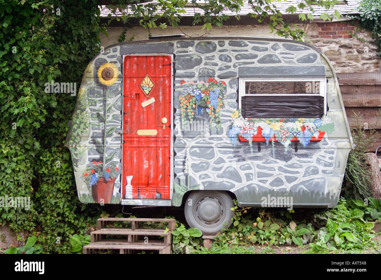 Decorated caravan.  Trompe l'oeil affect. In front of a stone wall. Craft centre. Llangollen. Wales. UK. (editorial Stock Photo