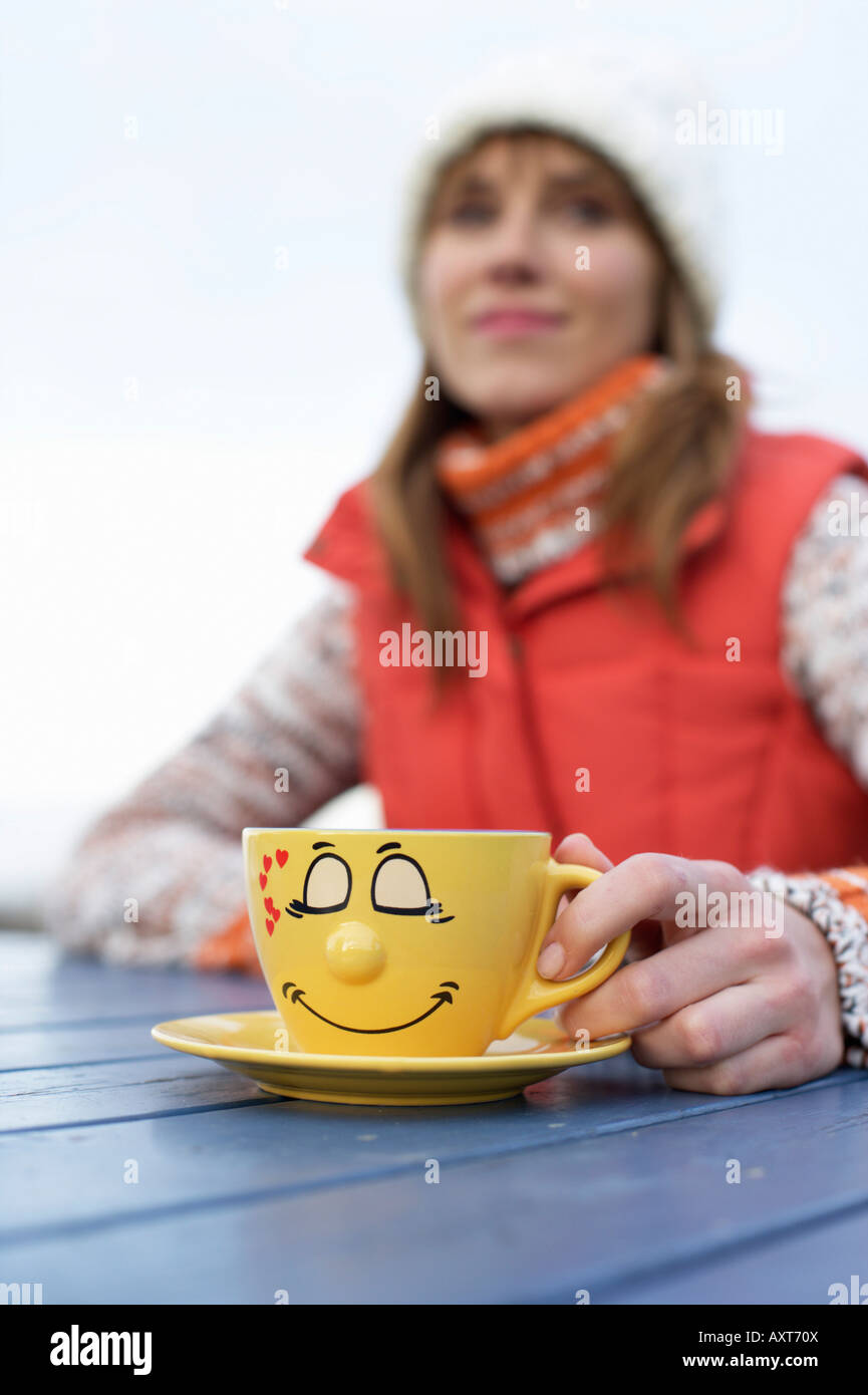 Young woman in warm clothing sitting outside at a table with a painted cup in her hand, selective focus - Stock Image
