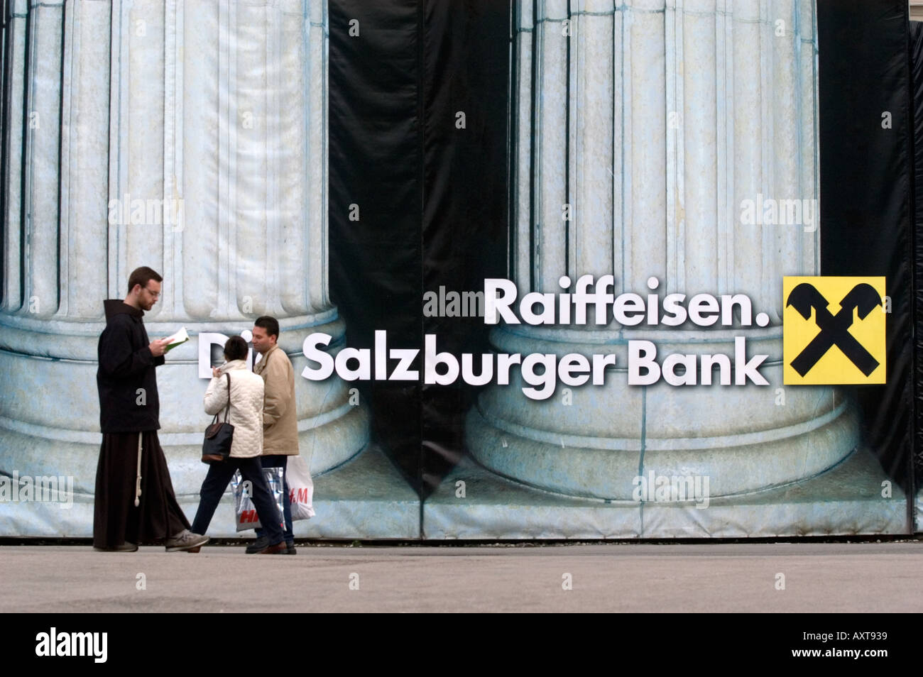 A monk and a couple walk past the Raiffeisen Bank undergoing refurbishment in Salzburg Austria - Stock Image