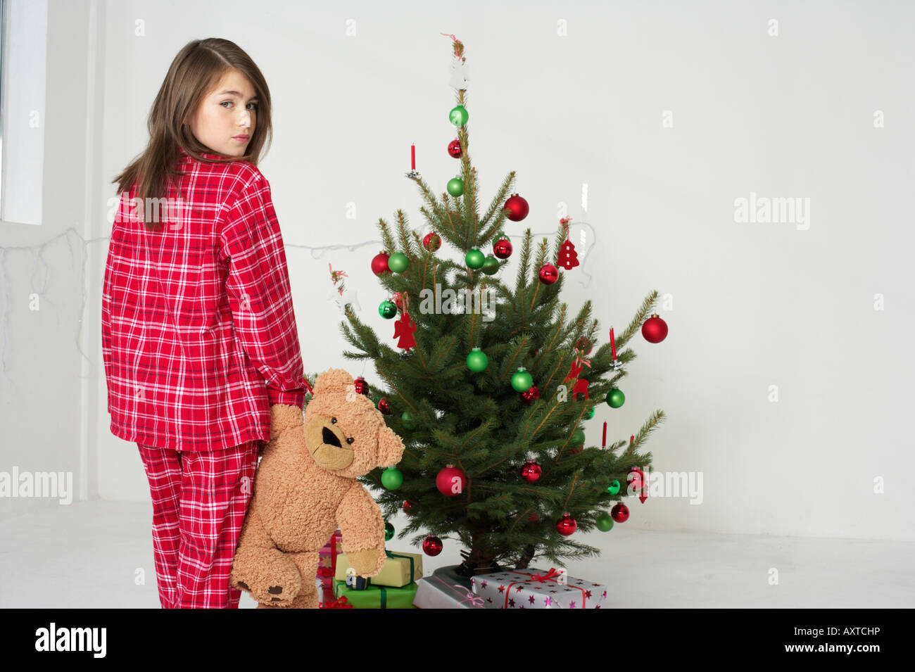 Girl wearing pajamas sneaking off to Christmas tree - Stock Image