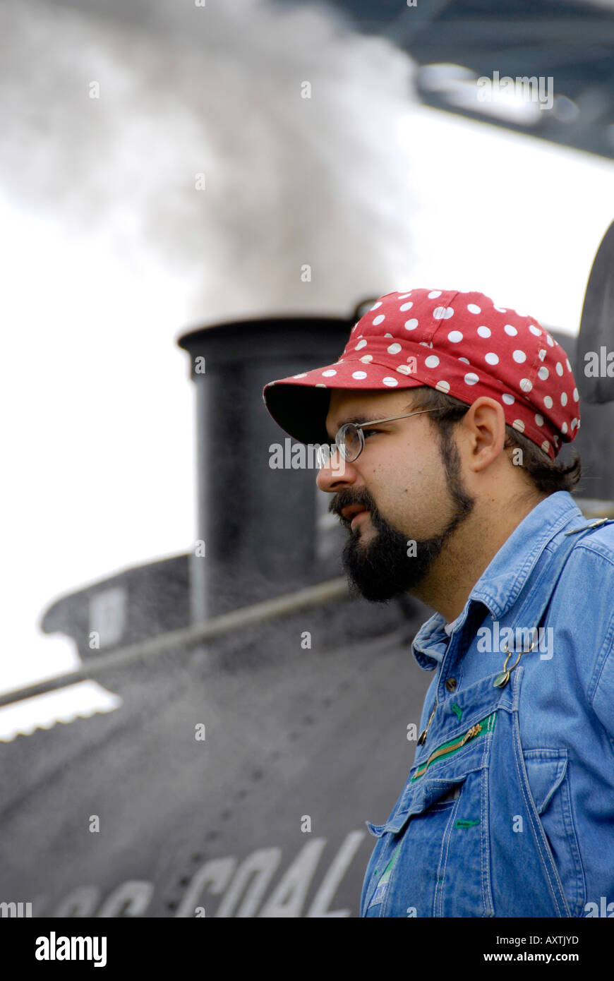 Historic steam Train locomotive engineer portrait with red and white pocodot hat - Stock Image