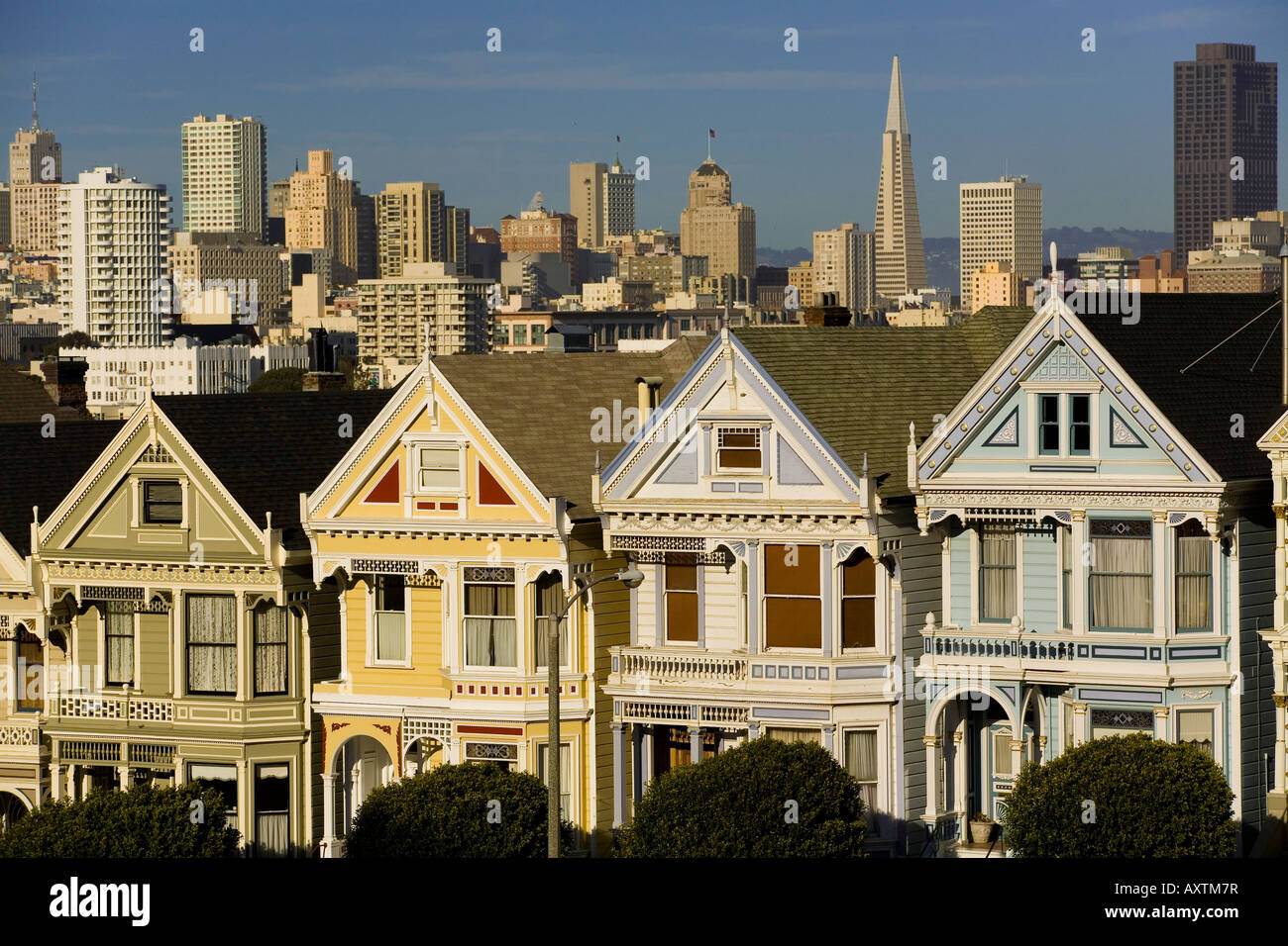 Restored Victorian houses and the San Francisco skyline. - Stock Image