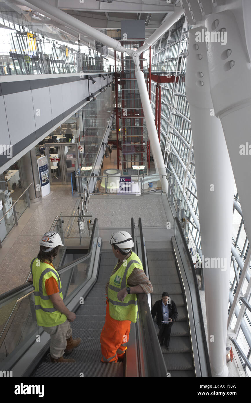 Construction workers on escalator in landside Arrivals area of newly opened London Heathrow Airport's Terminal - Stock Image