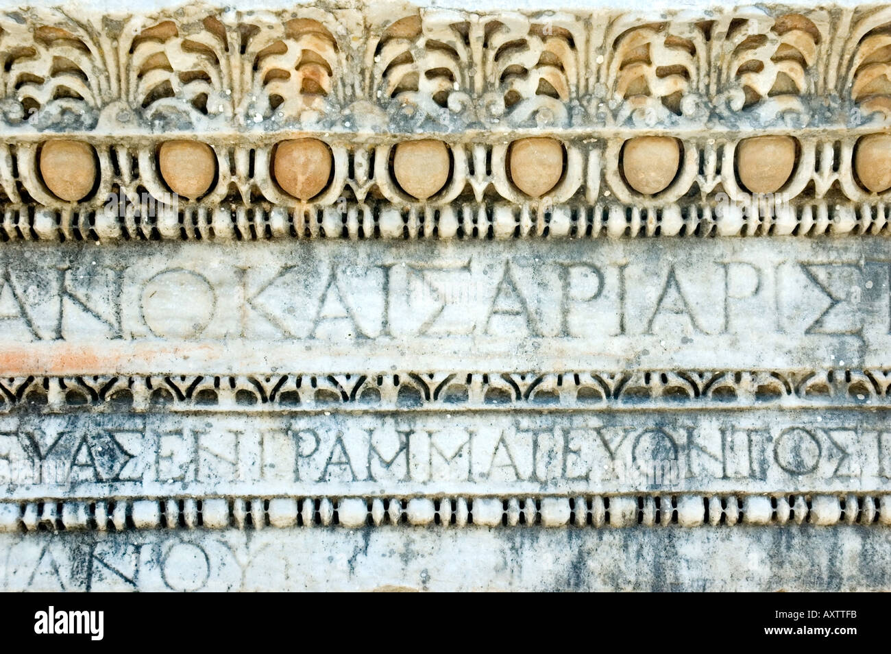 An intricately carved stone frieze depicting Greek writing and script design, in the city of Ephesus, Turkey. DSC_6700 - Stock Image