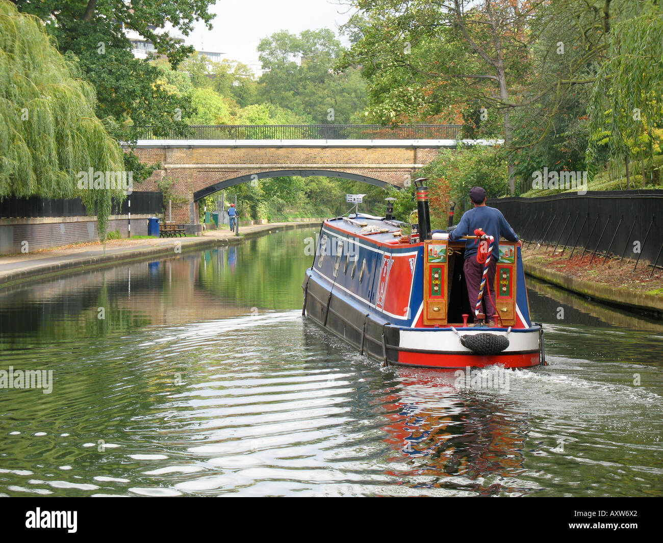 A man steers a narrowboat on the Regents Canal London England - Stock Image