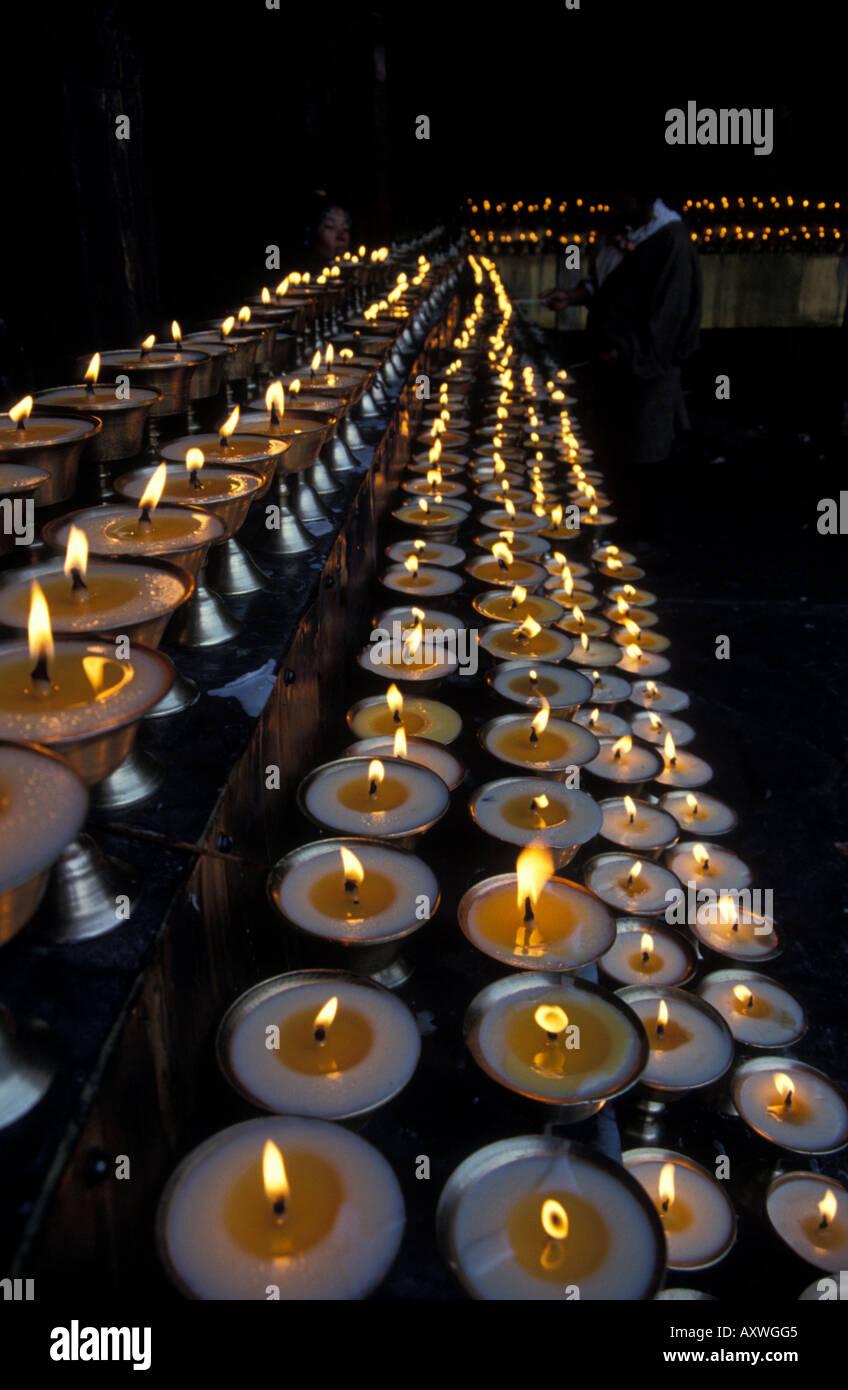 Tibetan Buddhist pilgrims lighting rows burning lit yak butter ... for lighting lamps in temple  75sfw