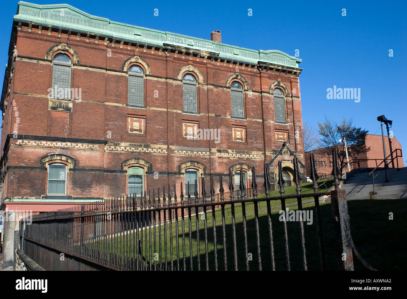 Old brick building and wrought iron fence in Saint John New Stock