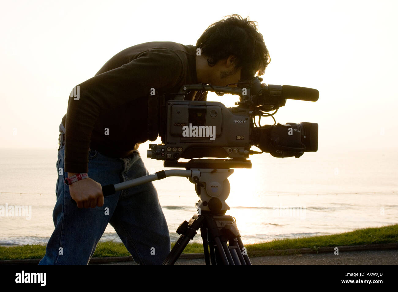 man student at Aberystwyth University TV and Film media studies with Sony video camera and tripod on location, UK - Stock Image