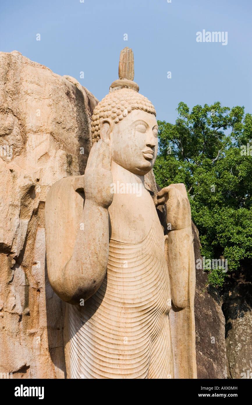 Giant standing statue of the Buddha, the left hand lifting the robe symbolising reincarnation, Aukana, Sri Lanka - Stock Image