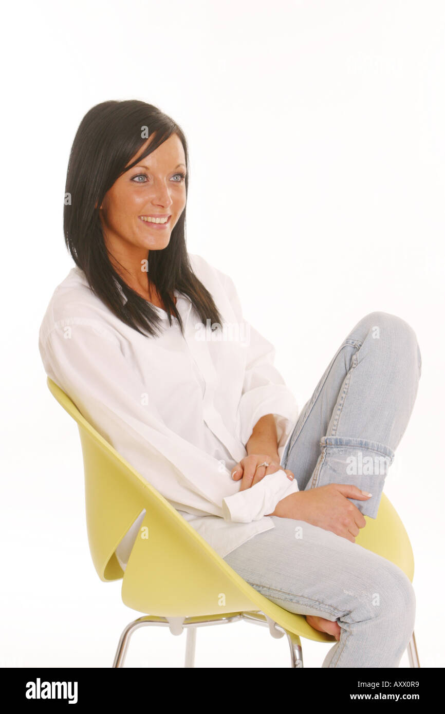 68ae24a302303 Girl woman in white top and grey leggings smiling sitting relaxed on yellow  chair one leg raised