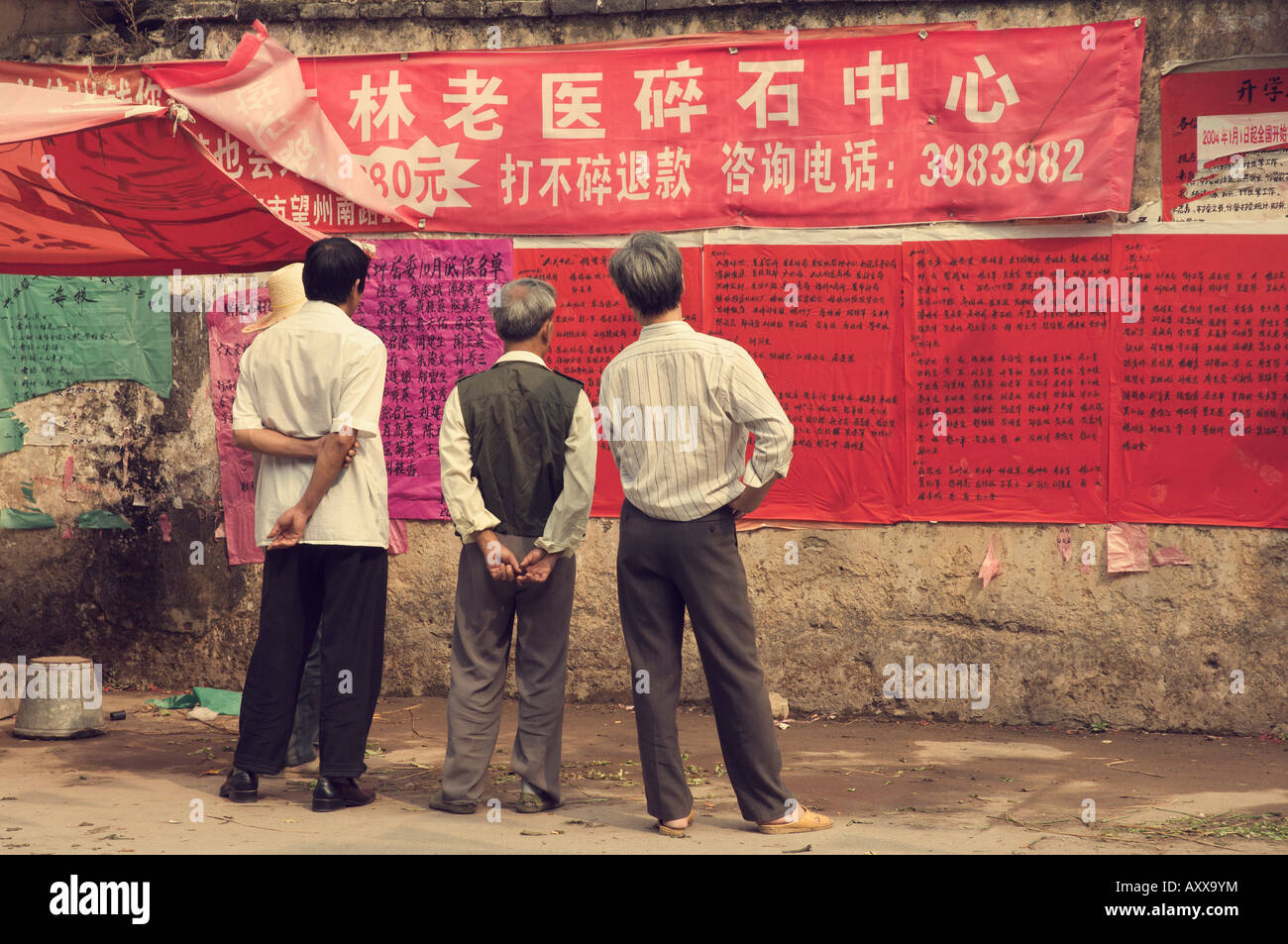 Chinese people reading announcement, Xingping, Guangxi Province, China, Asia - Stock Image