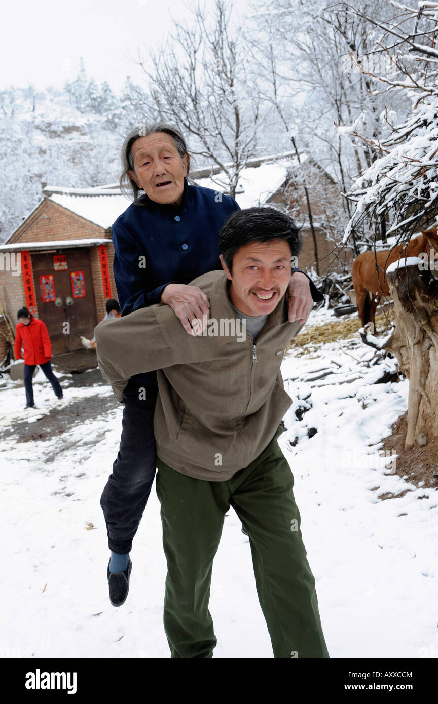 Man carries his mother in a village in Hebei province, China. 28-Mar-2008 - Stock Image