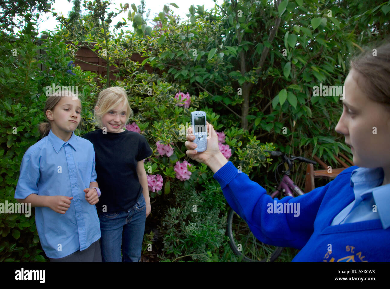young girls smiling cheekily photographed by mobile phone camera - Stock Image
