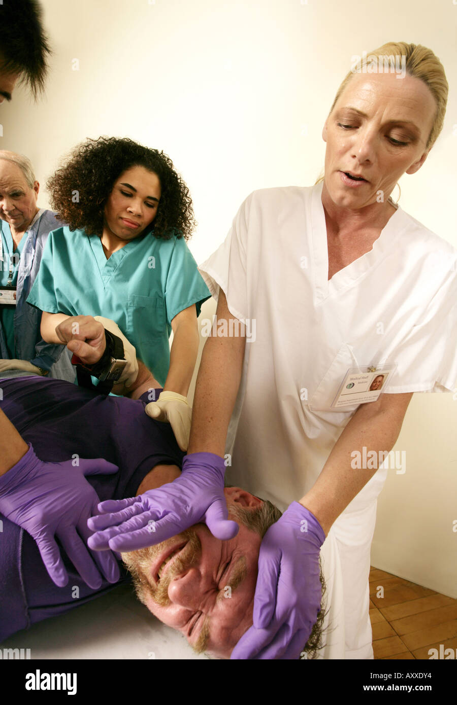 Nurse leads team to carefully restrain patient. Stock Photo