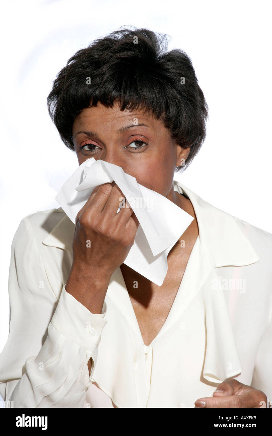 Woman blows her nose using tissue. - Stock Image