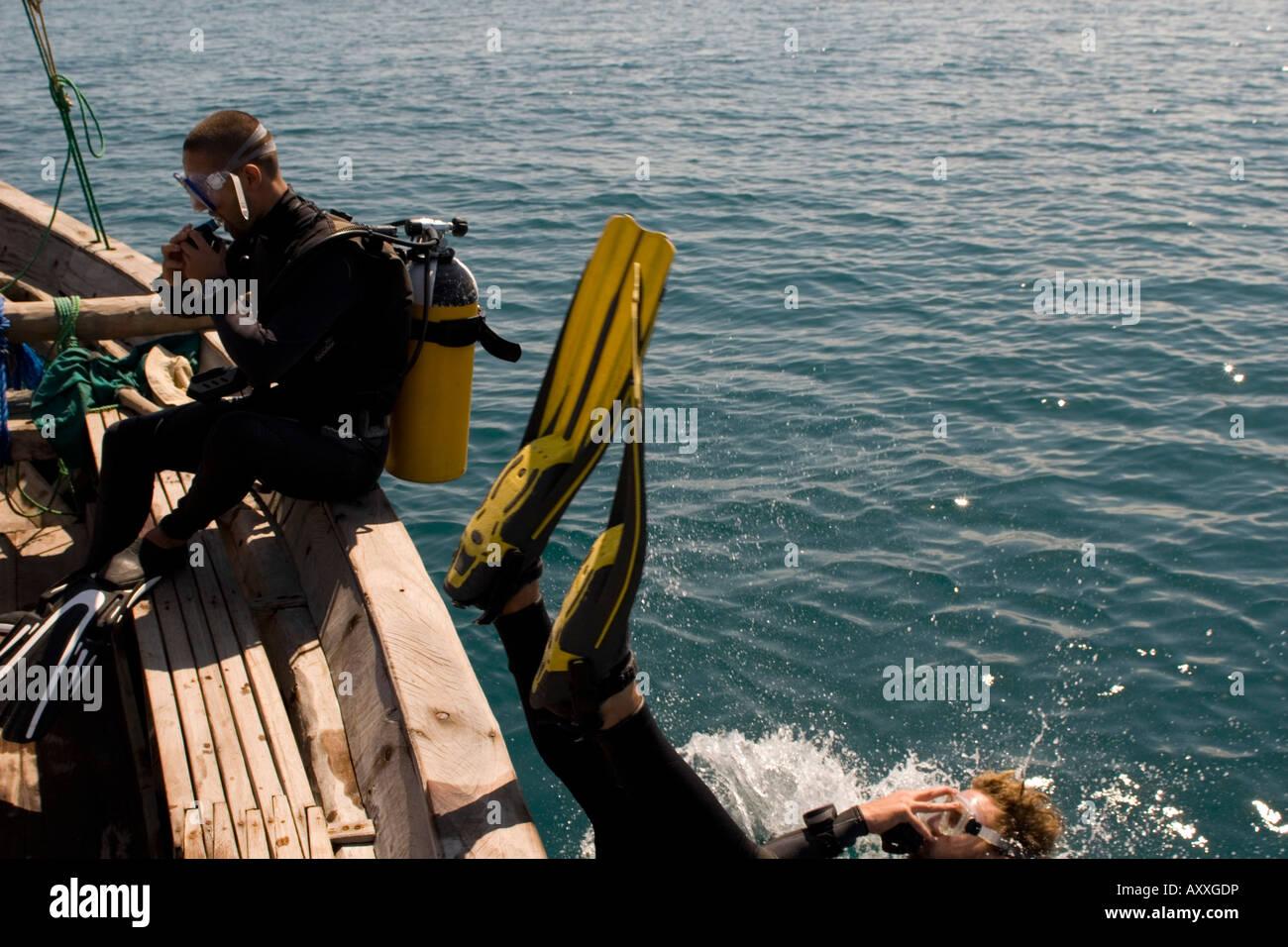Scuba divers entering water from boat Chole Bay off Mafia Island Tanzania - Stock Image