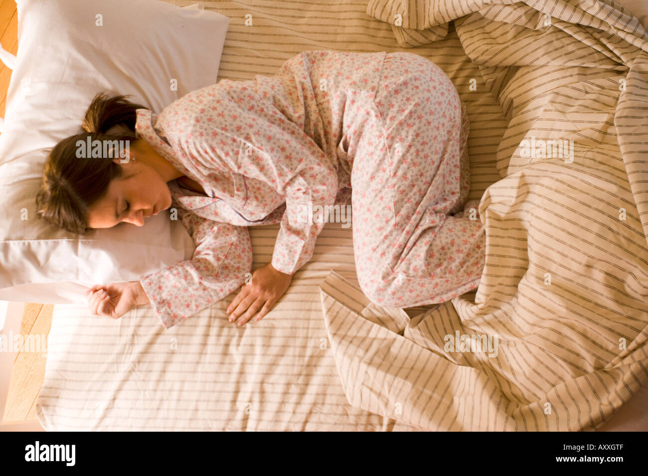 Woman sleeping in the fetal position in her pajamas in bed. - Stock Image