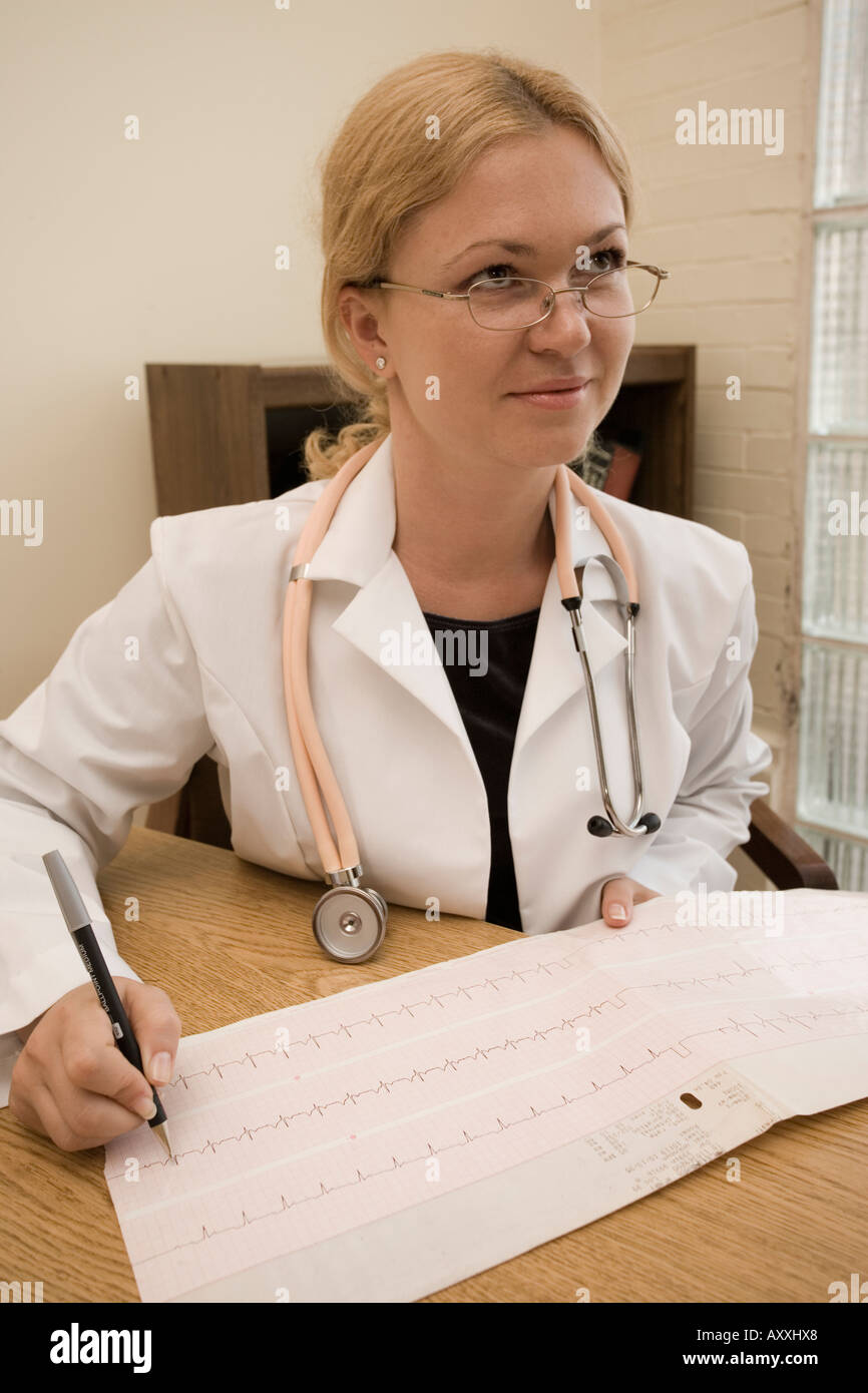 Portrait of a white female physician or doctor (played by a model) in her office reading an EKG or ECG cardiac printout. - Stock Image