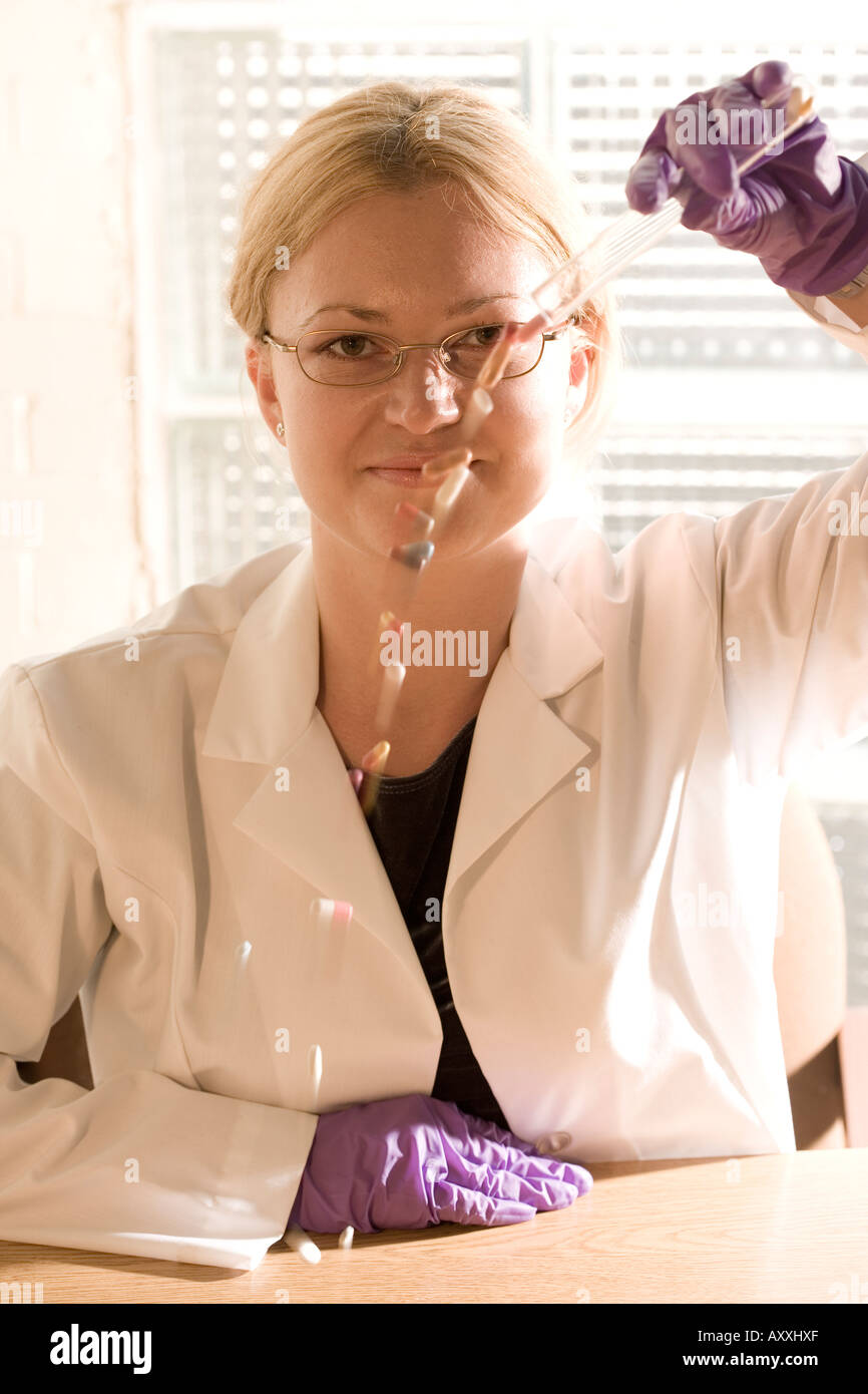 Research scientist (played by a model) pours pills from a testtube. - Stock Image