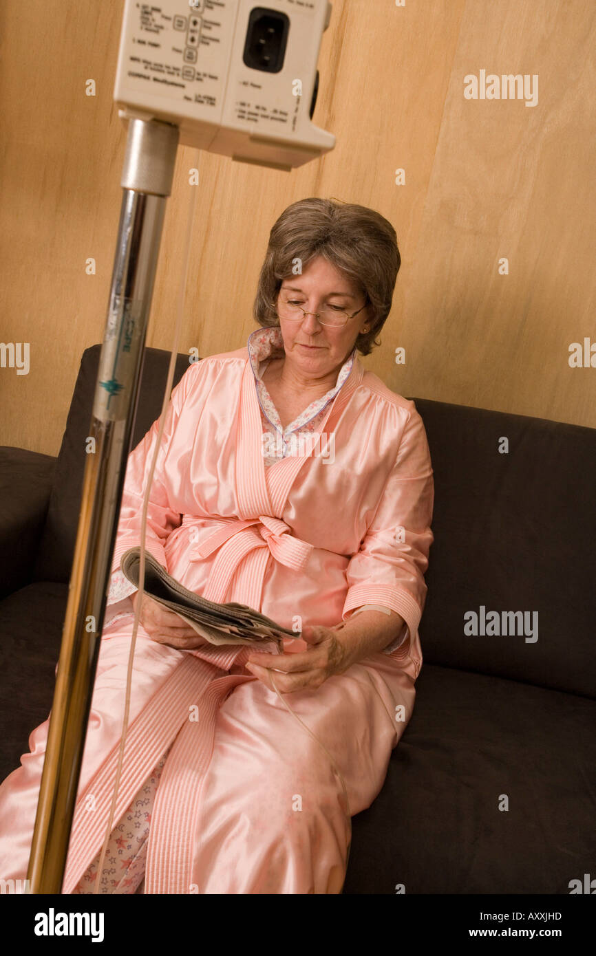 Elderly woman sits waiting while food is delivered to her via solution. - Stock Image