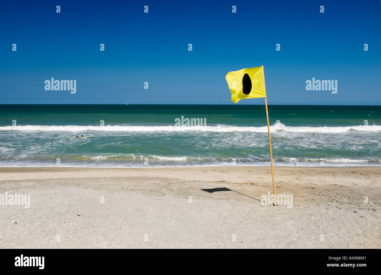 I flag Rule 30 1 Around the ends rule is in effect yellow flag with black dot circle solid round on beach - Stock Image