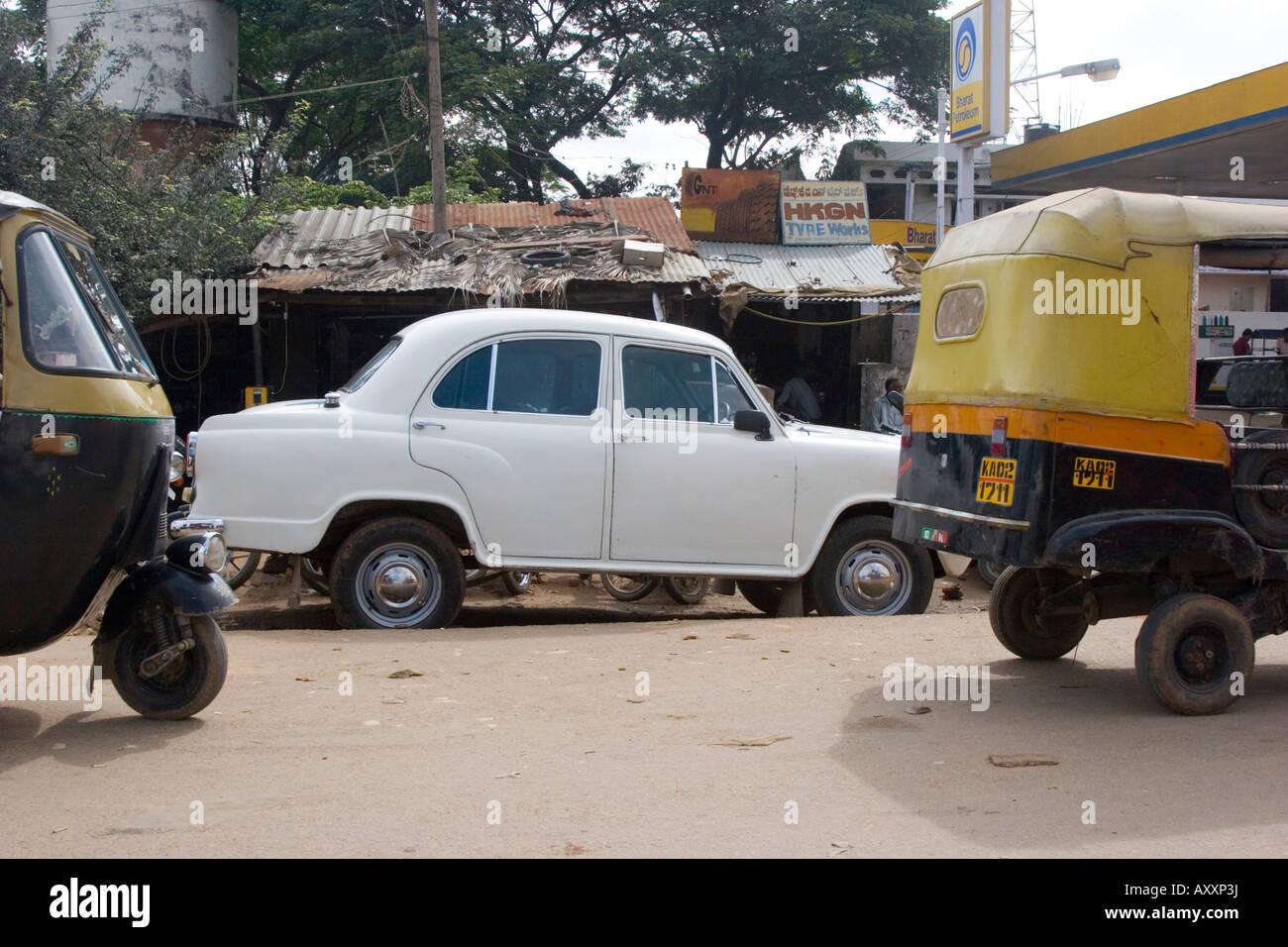 Hindustan Ambassador car parked between two auto rickshaws - Stock Image