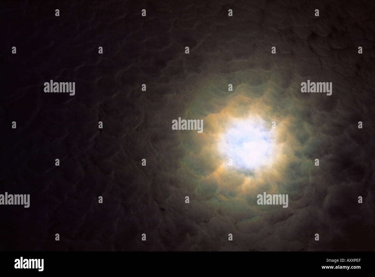 Light hole through thin cloud cover showing moon moonshine halo in night sky - Stock Image