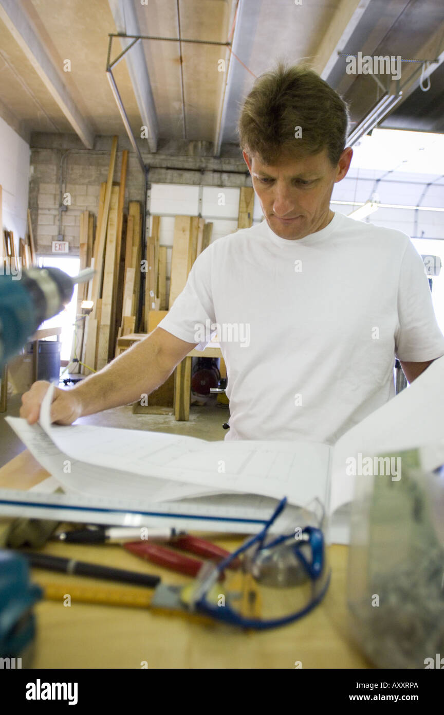 Business owner regular job woodworking cabinet maker man working business owner regular job woodworking cabinet maker man working self employed people person at work plans blueprints malvernweather Gallery