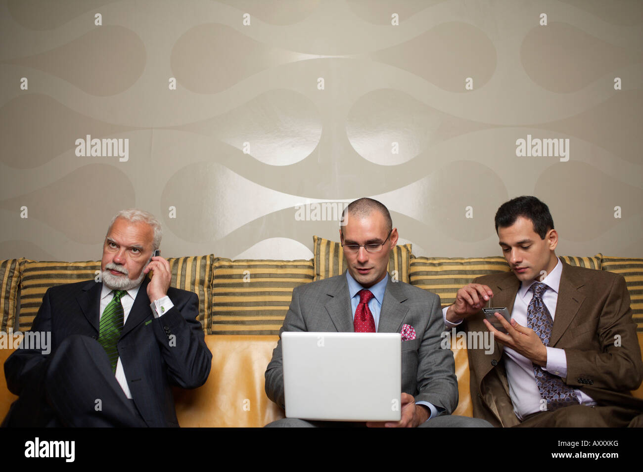 Three businessmen on a sofa with different communication devices - Stock Image
