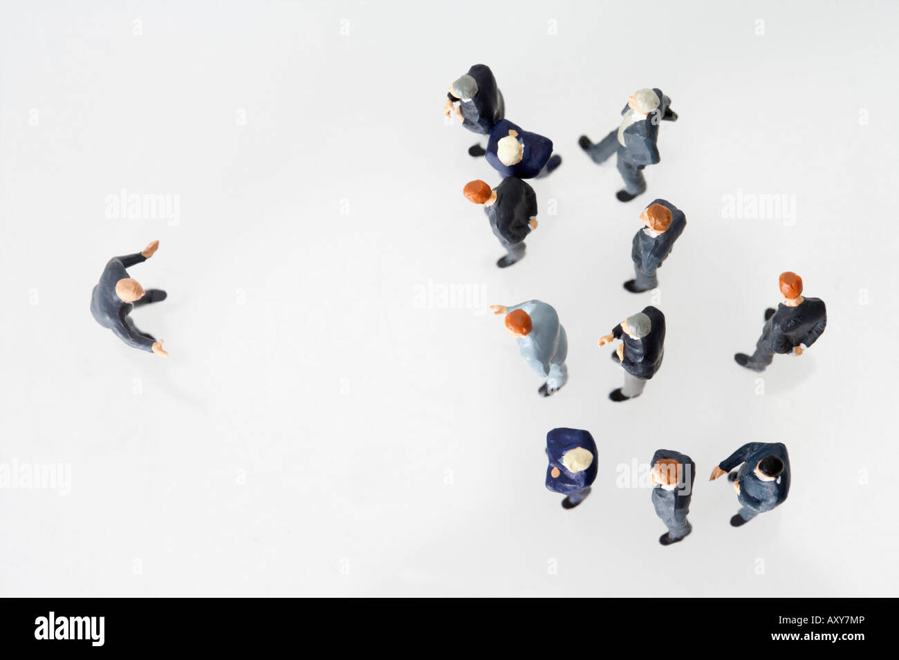 Group of businessmen figurines and one businessman figurine standing vis-à-vis - Stock Image