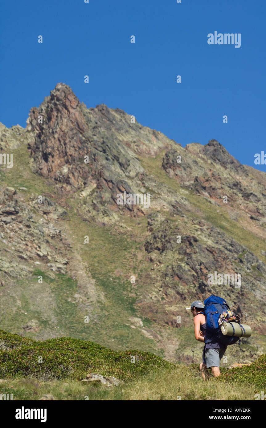 Hiker on climbing trail in hiking area of Pic de Coma Pedrosa, Andorra's highest mountain, Parish of La Massana, - Stock Image
